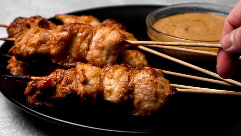 Chicken skewers served on a plate with Satay sauce.