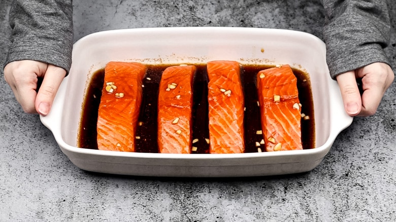 Salmon ready to be baked in dish.